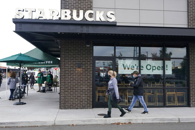 Customers walk past a sign that reads