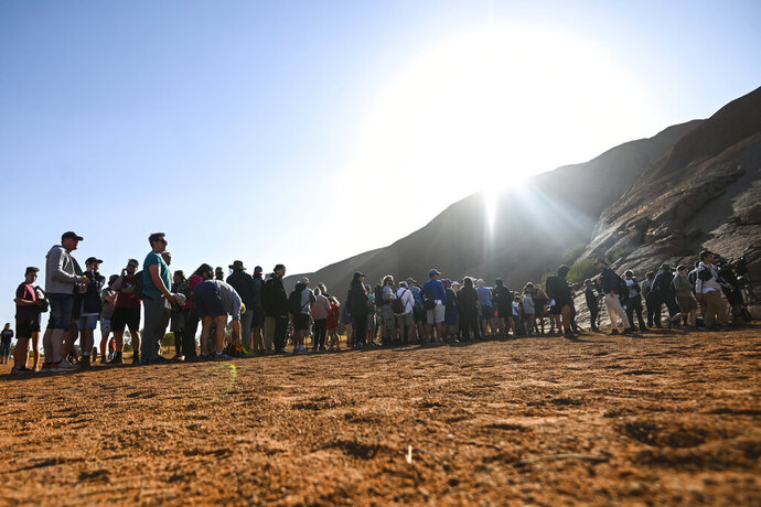 Tourists line up waiting to climb the sandstone monolith called Uluru that dominates Australia's arid center at Uluru-Kata Tjuta National Park, Friday, Oct. 25, 2019, the last day climbing is allowed. The end of visitors enjoying the panoramic views of the incongruously flat Outback surrounds from the rock's summit also marks indigenous Australians finding a new voice in national decision-making. (Lukas Coch/AAP Image via AP)