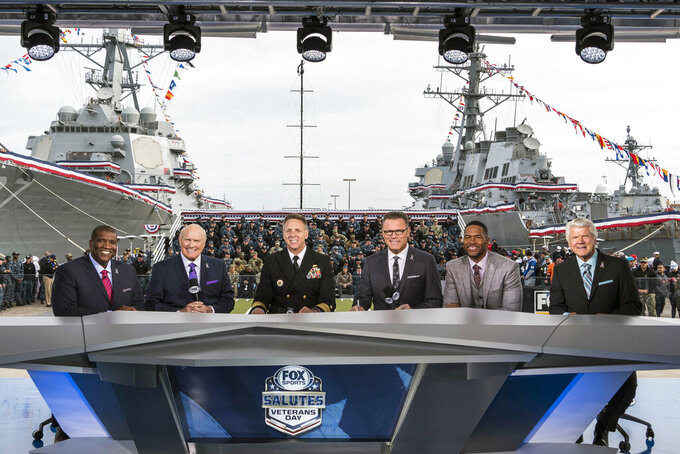 "In this 2017 photo provided by Fox Sports, from left to right, Curt Menefee, Terry Bradshaw, Adm. Phil Davidson, commander of U.S. Fleet Forces, Howie Long, Michael Strahan and Jimmy Johnson pose during the ""Fox NFL Sunday"" pregame show at Naval Station-Norfolk. This year's Salute to Veterans Day show will originate from the U.S. Military Academy at West Point. (Jen Pransky/Fox Sports via AP)"