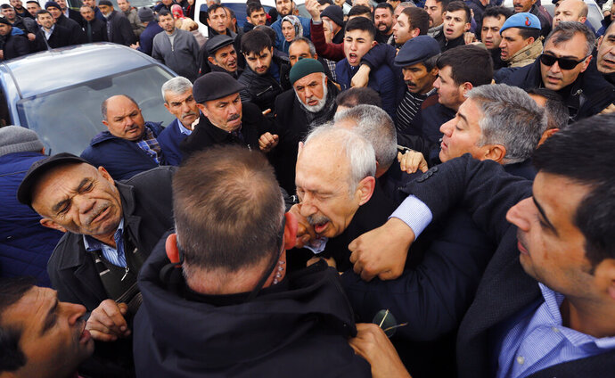 A man punches Kemal Kilicdaroglu, the leader of Turkey's main opposition Republican People's Party, during the funeral of a soldier who was slain during clashes with Kurdish rebels at Iraq border, outside Ankara, Turkey, Sunday, April 21, 201. The politician was not hurt, party officials said. Protestors at a village outside of Ankara threw punches at Kemal Kilicdaroglu as security officials tried to escort him away from the crowd, television footage showed. (DHA via AP)