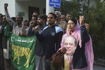 Supporters of Pakistan's ailing former Prime Minister Nawaz Sharif shout slogans at an airport in Lahore, Pakistan, Tuesday, Nov. 19, 2019. Sharif has arrived at the airport to board a plane after a court granted him permission to leave for four weeks abroad for medical treatment. (AP Photo/K.M. Chaudary)