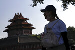 A woman puts down her face mask walks by the Turret of the Forbidden City in Beijing, Thursday, Aug. 13, 2020. New local cases in China fell into the single digits, while Hong Kong saw another rise in hospitalizations and deaths. (AP Photo/Andy Wong)