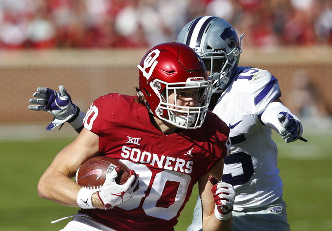 Kansas State defensive back Walter Neil Jr. (15) moves in to tackle Oklahoma tight end Grant Calcaterra (80) in the first half of an NCAA college football game in Norman, Okla., Saturday, Oct. 27, 2018. (AP Photo/Sue Ogrocki)