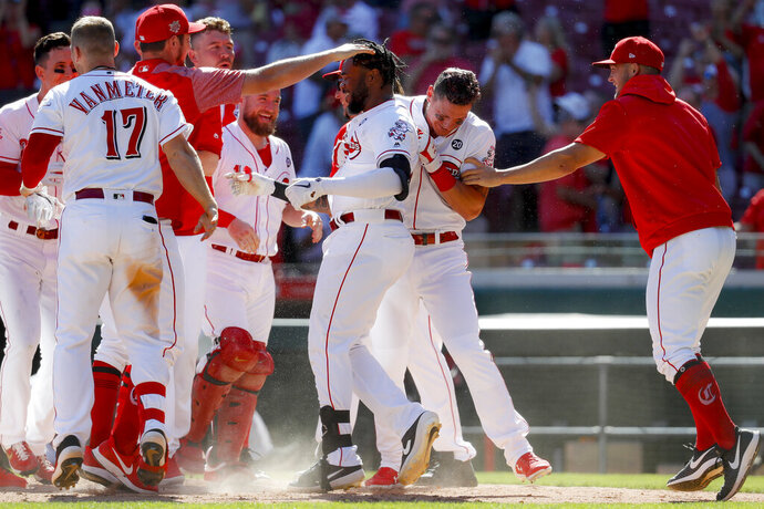 Cincinnati Reds' Phillip Ervin, center, celebrates with his teammates after hitting a walkoff solo home run on Philadelphia Phillies relief pitcher Nick Vincent in the 11th inning of a baseball game, Thursday, Sept. 5, 2019, in Cincinnati. (AP Photo/John Minchillo)