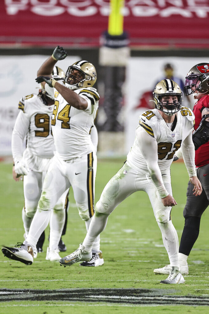 New Orleans Saints defensive end Cameron Jordan (94) and defensive end Trey Hendrickson (91) celebrate a turnover during an NFL game against the Tampa Bay Buccaneers, Sunday, Nov. 8, 2020 in Tampa, Fla. The Saints defeated the Buccaneers 38-3. (Margaret Bowles via AP)