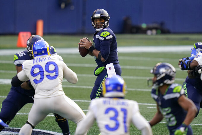 Seattle Seahawks quarterback Russell Wilson (3) looks to pass during the first half of an NFL football game against the Los Angeles Rams, Sunday, Dec. 27, 2020, in Seattle. (AP Photo/Elaine Thompson)