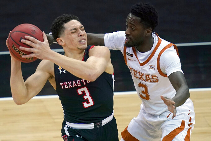 Texas Tech Red guard Clarence Nadolny, left, is covered by Texas guard Courtney Ramey, right, during the first half of an NCAA college basketball game in the quarterfinal round of the Big 12 men's tournament in Kansas City, Mo., Thursday, March 11, 2021. (AP Photo/Orlin Wagner)