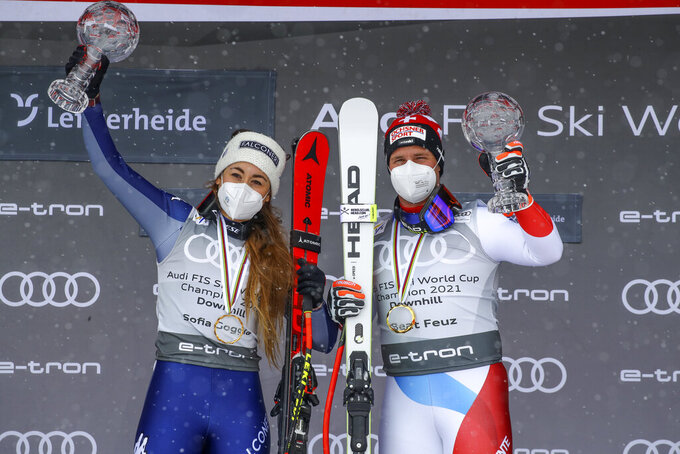 Switzerland's Beat Feuz, right, winner of the alpine ski, men's World Cup downhill discipline trophy, poses with Italy's Sofia Goggia, the winner of the women's discipline trophy, in Lenzerheide, Switzerland, Wednesday, March 17, 2021. (AP Photo/Marco Trovati)