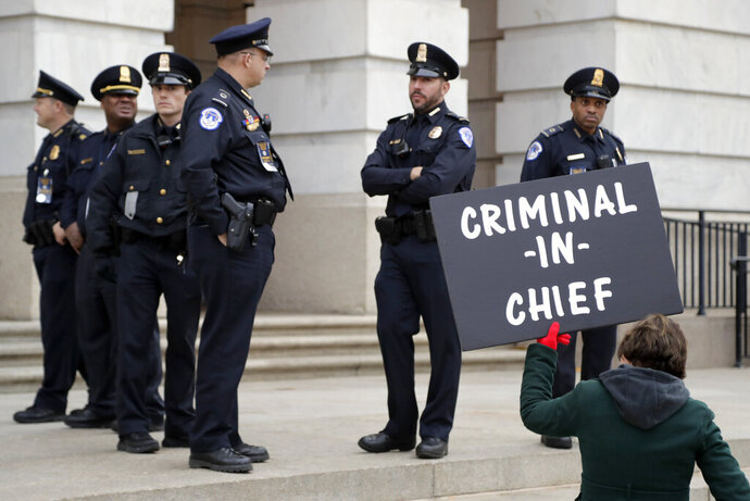 Capitol Police officers stand near a demonstrator holding a sign outside of Longworth House Office Building, where former White House national security aide Fiona Hill and David Holmes, a U.S. diplomat in Ukraine, are testifying before the House Intelligence Committee on Capitol Hill in Washington, Thursday, Nov. 21, 2019, during a public impeachment hearing of President Donald Trump's efforts to tie U.S. aid for Ukraine to investigations of his political opponents. (AP Photo/Julio Cortez)