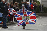 Royal fan John Loughery displays a banner as people wait for the Royal Regiment of Scotland band, on the high street, in Windsor, south England, Tuesday, May 7, 2019, a day after Prince Harry announced that his wife Meghan, Duchess of Sussex, had given birth to a boy. The as-yet-unnamed baby arrived less than a year after Prince Harry wed Meghan Markle in a spectacular televised event on the grounds of Windsor Castle that was watched the world over. (AP Photo/Alastair Grant)