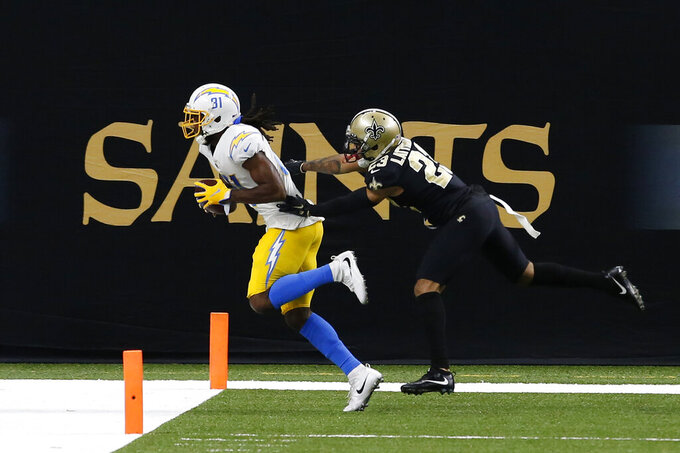 Los Angeles Chargers wide receiver Mike Williams (81) pulls in a touchdown reception against New Orleans Saints cornerback Marshon Lattimore (23) in the first half of an NFL football game in New Orleans, Monday, Oct. 12, 2020. (AP Photo/Butch Dill)