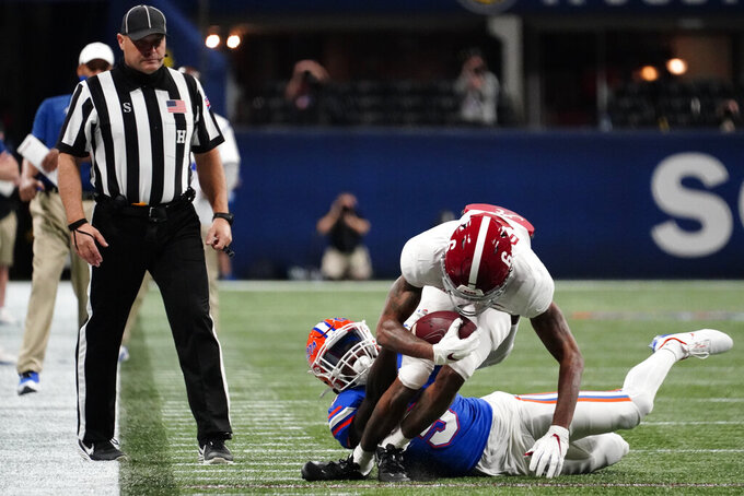 Alabama wide receiver DeVonta Smith (6) is hit by Florida defensive lineman Gervon Dexter (9) during the first half of the Southeastern Conference championship NCAA college football game, Saturday, Dec. 19, 2020, in Atlanta. (AP Photo/Brynn Anderson)