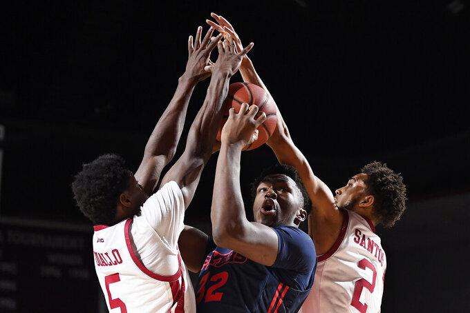 Massachusetts' Samba Diallo (5) and Preston Santos (2) guard Dayton's Jordy Tshimanga (32) in the first half of an NCAA college basketball game, Saturday, Feb. 15, 2020, in Amherst, Mass. (AP Photo/Jessica Hill)