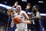 Xavier's Zach Hankins, center, eyes the basket against Georgetown's Jessie Govan (15) during the first half of an NCAA college basketball game, Wednesday, Jan. 9, 2019, in Cincinnati. (AP Photo/John Minchillo)