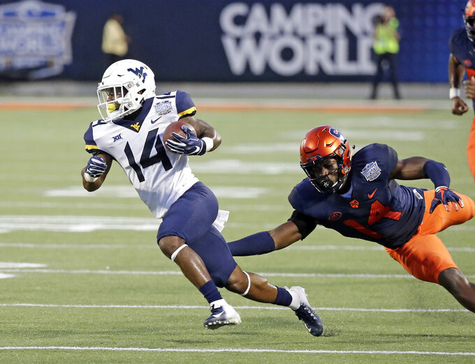 West Virginia running back Tevin Bush, left, gains yardage as he gets past Syracuse defensive back Evan Foster during the first half of the Camping World Bowl NCAA college football game Friday, Dec. 28, 2018, in Orlando, Fla. (AP Photo/John Raoux)