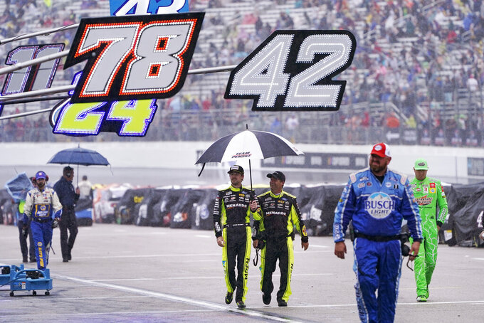 Kyle Busch, far right, with other drivers and race officials, walks down pit road during a rain delay at a NASCAR Cup Series auto race, Sunday, July 18, 2021, in Loudon, N.H. (AP Photo/Charles Krupa)