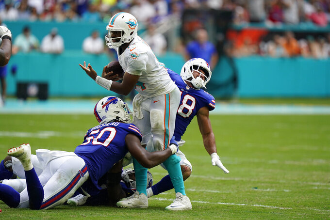 Miami Dolphins quarterback Jacoby Brissett (14) is sacked by Buffalo Bills defensive end Greg Rousseau (50) and Buffalo Bills outside linebacker Matt Milano (58) during the first half of an NFL football game, Sunday, Sept. 19, 2021, in Miami Gardens, Fla. (AP Photo/Wilfredo Lee)