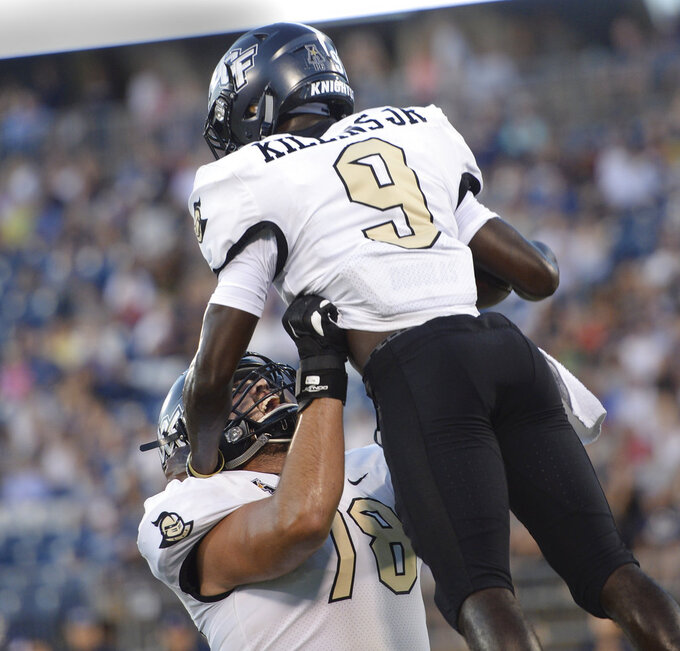 Central Florida running back Adrian Killins Jr. (9) is congratulated by offensive lineman Wyatt Miller after scoring a touchdown during the first half of an NCAA college football game against Connecticut on Thursday, Aug. 30, 2018, in East Hartford, Conn. (AP Photo/Stephen Dunn)