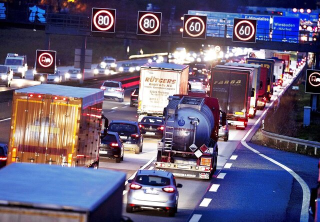 FILE - In this Tuesday, Dec. 4, 2018 file photo, trucks line up on a highway in Frankfurt, Germany. Germany's parliament is poised to more than double the starting price for carbon dioxide emissions from the transport and heating industries when the charge is introduced in 2021. (AP Photo/Michael Probst, file)