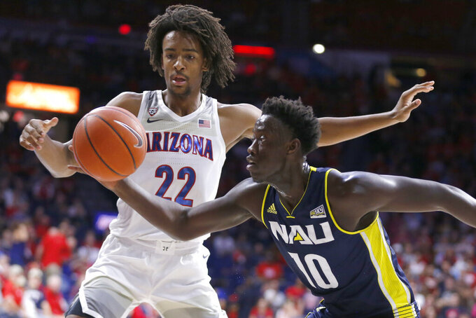 Northern Arizona forward Bernie Andre (10) drives past Arizona forward Zeke Nnaji during the first half of an NCAA college basketball game Wednesday, Nov. 6, 2019, in Tucson, Ariz. (AP Photo/Rick Scuteri)