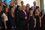 President Donald Trump stands with members of Queens University of Charlotte Swim Team during the NCAA Collegiate National Champions Day at the White House, Friday, Nov. 22, 2019, in Washington. (AP Photo/ Evan Vucci)