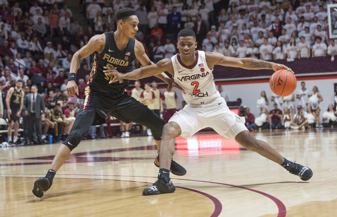 Virginia Tech guard Landers Volley (2) keeps ball away from Florida State defender Devin Vassell (24) during the second half of an NCAA college basketball game in Blacksburg, Va., Saturday, Feb. 1, 2020. (AP Photo/Lee Luther Jr.)