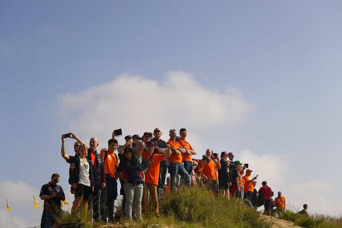 Orange-clad fans wait on a dune to watch the first free practice ahead of Sunday's Formula One Dutch Grand Prix at the Zandvoort racetrack, Netherlands, Friday, Sept. 3, 2021. (AP Photo/Francisco Seco)