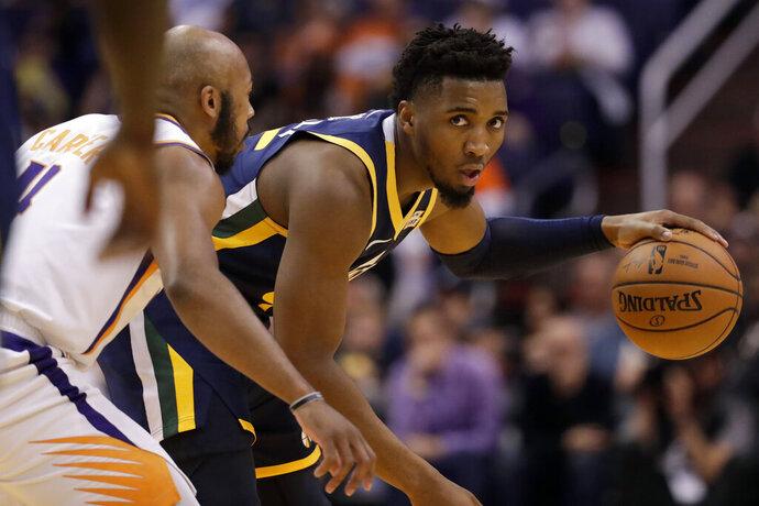 Utah Jazz guard Donovan Mitchell, right, looks to pass as Phoenix Suns guard Jevon Carter (4) defends during the first half of an NBA basketball game, Monday, Oct. 28, 2019, in Phoenix. (AP Photo/Matt York)