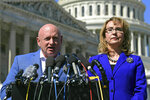 FILE - In this Oct. 2, 2017, file photo, former Rep. Gabrielle Giffords, D-Ariz., right, listens as her husband, retired astronaut Mark Kelly, left, speaks on Capitol Hill in Washington. Kelly entered the race Tuesday, Feb. 12, 2019 to finish John McCain's term in the U.S. Senate, looking to join a small club of astronauts who have traded an office in outer space for the U.S. Capitol. (AP Photo/Susan Walsh, File)