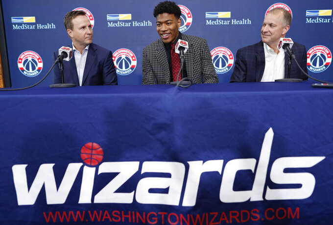 FILE - In this June 21, 2019, file photo, the Washington Wizards draft pick Rui Hachimura, of Japan, center, smiles during an introductory press conference with head coach Scott Brooks, left, and Senior Vice President of Basketball Operations Tommy Sheppard at Capital One Arena in Washington.  The Washington Wizards won't have Bradley Beal, John Wall or Davis Bertans when the NBA returns amid the coronavirus pandemic. That leaves a bunch of young players, led by rookie Rui Hachimura, the first Japanese player to be taken in the first round of the NBA draft. (AP Photo/Pablo Martinez Monsivais, File)