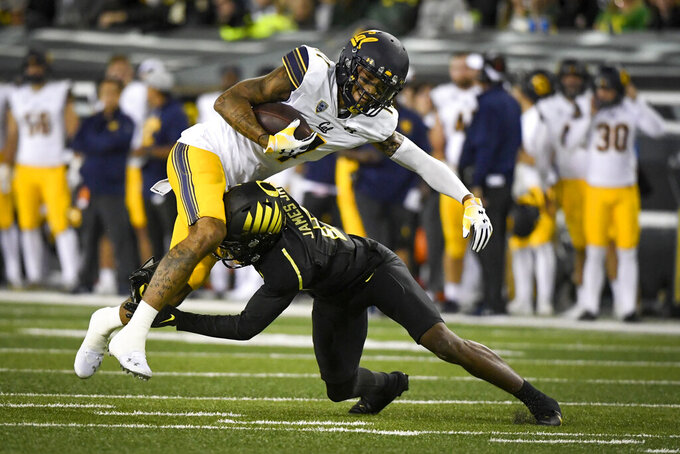 California wide receiver Kekoa Crawford is tackled by Oregon cornerback DJ James during the first quarter of an NCAA college football game Friday, Oct. 15, 2021, in Eugene, Ore. (AP Photo/Andy Nelson)