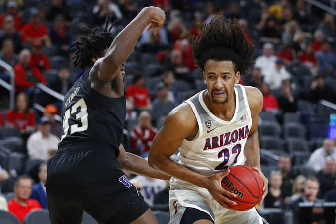 Arizona's Zeke Nnaji (22) drives into Washington's Isaiah Stewart (33) during the second half of an NCAA college basketball game in the first round of the Pac-12 men's tournament Wednesday, March 11, 2020, in Las Vegas. (AP Photo/John Locher)