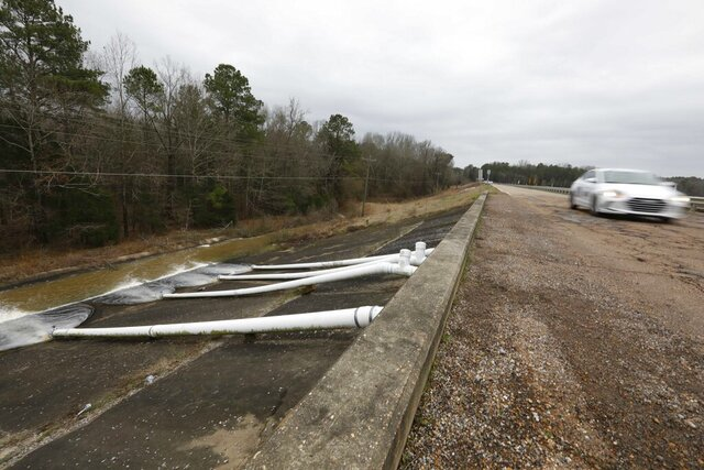 A car speeds past the additional drainage pumps on the Oktibbeha County Lake dam near Starkville, Miss., Wednesday afternoon, Jan. 15, 2020. Officials are hoping the additional drainage will limit the heavy pressure the rain-swollen lake is placing on the dam. County officials believe a breach would affect an estimated 130 properties and several highways. (AP Photo/Rogelio V. Solis)