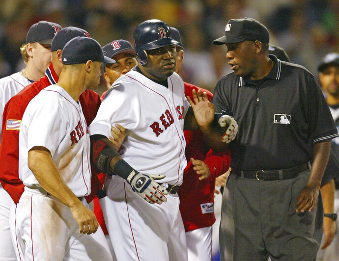 FILE - In this Aug. 17, 2004, file photo, Boston Red Sox David Ortiz, center, is restrained by teammates and umpire Chuck Meriwether after being hit by a pitch from Toronto Blue Jays pitcher Ted Lilly during the seventh inning of a baseball game at Fenway Park in Boston. Meriwether, a former major league umpire who had been ill with cancer, died Saturday, Oct. 26, 2019, at his home in Nashville, Tenn. He was 63. Meriwether called his first big league game in 1987, was promoted to the full-time American League staff in 1993 and worked for 18 years. He then became a major league umpire supervisor for nine years. (AP Photo/Winslow Townson, File)