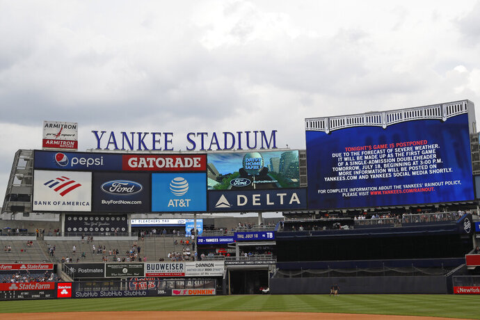 A sign advises fans that Wednesday's scheduled baseball game between the New York Yankees and the Tampa Bay Rays has been postponed due to the possibility of inclement weather, Wednesday, July 17, 2019, in New York. The game will be played Thursday afternoon as part of a single-admission doubleheader. (AP Photo/Kathy Willens)