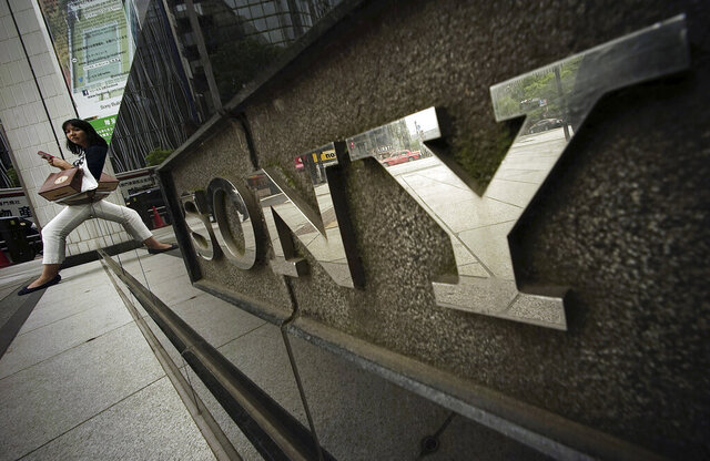 FILE - In this April 30, 2015, file photo, a woman sits near the logo of Sony Corp. in Tokyo. Japanese electronics and entertainment company Sony Corp. said Tuesday that its April-June profit jumped 53% as its video-game and other online businesses thrived with people staying home due to the coronavirus pandemic. (AP Photo/Eugene Hoshiko, File)
