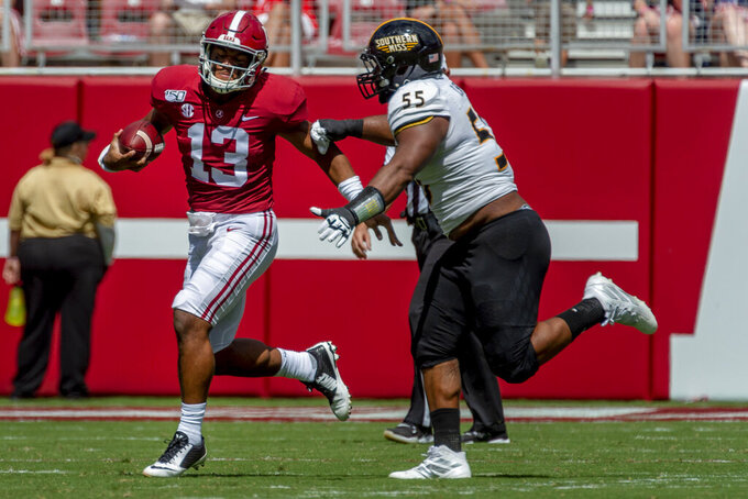 Alabama quarterback Tua Tagovailoa (13) runs the ball past Southern Miss defensive lineman Demarrio Smith (55) during the first half of an NCAA college football game, Saturday, Sept. 21, 2019, in Tuscaloosa, Ala. (AP Photo/Vasha Hunt)
