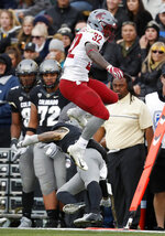 Washington State running back James Williams, top, jumps over Colorado defensive back Dante Wigley in the second half of an NCAA college football game Saturday, Nov. 10, 2018, in Boulder, Colo. Washington State won 31-7. (AP Photo/David Zalubowski)