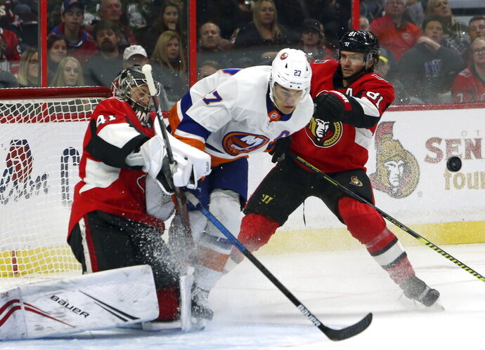 Ottawa Senators defenseman Ron Hainsey (81) checks New York Islanders center Anders Lee (27) into Senators goaltender Craig Anderson (41) during second-period NHL hockey game action in Ottawa, Ontario, Friday, Oct. 25, 2019. (Fred Chartrand/The Canadian Press via AP)