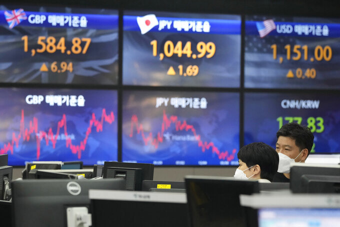 Currency traders watch monitors at the foreign exchange dealing room of the KEB Hana Bank headquarters in Seoul, South Korea, Friday, July 23, 2021. Asian markets were mixed on Friday after major indexes edged higher on Wall Street, preserving their gains for the week. (AP Photo/Ahn Young-joon)
