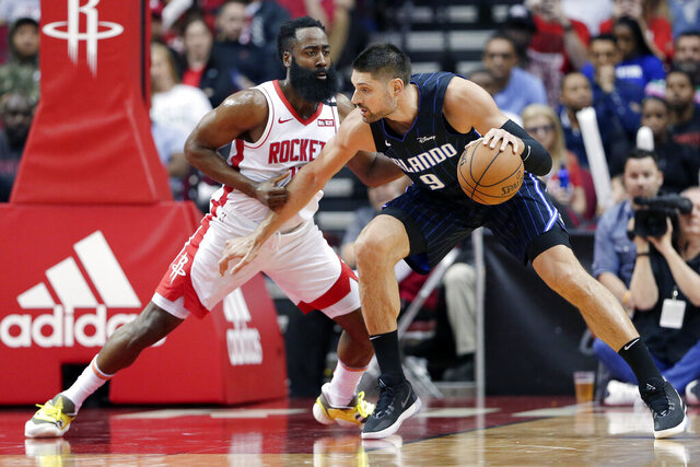Orlando Magic center Nikola Vucevic (9) attempts to drive around Houston Rockets guard James Harden, left, during the first half of an NBA basketball game Sunday, March 8, 2020, in Houston. (AP Photo/Michael Wyke)