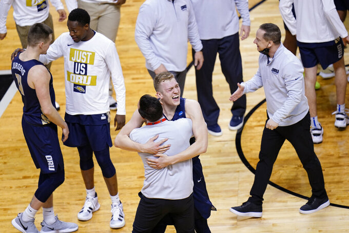 Oral Roberts forward Francis Lacis, center, celebrates with a coach after a college basketball game against Florida in the second round of the NCAA tournament at Indiana Farmers Coliseum, Sunday, March 21, 2021 in Indianapolis. Oral Roberts won 81-78. (AP Photo/AJ Mast)