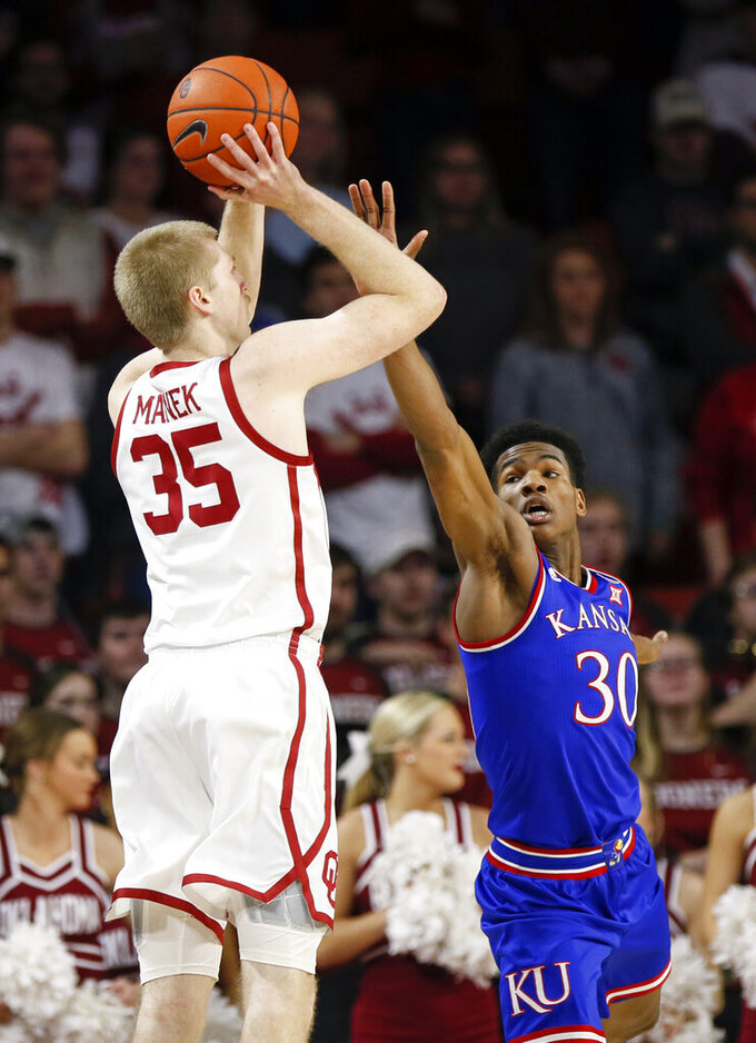 Oklahoma forward Brady Manek (35) shoots as Kansas guard Ochai Agbaji (30) defends in the first half of an NCAA college basketball game in Norman, Okla., Tuesday, March 5, 2019. (AP Photo/Nate Billings)