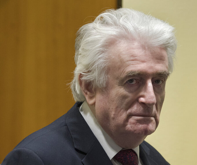 FILE - In this Wednesday, March 20, 2019 file photo, former Bosnian Serb leader Radovan Karadzic enters the court room of the International Residual Mechanism for Criminal Tribunals in The Hague, Netherlands. The British government said Wednesday, May 12, 2021 that former Bosnian Serb leader Radovan Karadzic will serve his life sentence for war crimes in a U.K. prison. Karadzic, one of the chief architects of the slaughter and devastation of Bosnia's 1992-95 war, was convicted in 2016 by a United Nations court of genocide, crimes against humanity and war crimes. (AP Photo/Peter Dejong, file)
