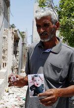 Nasser Abu Fares, who lost three of his daughters and his 9-month-old grandson when an Israeli artillery bombardment hit his family house during the 11-day war between Israel and Gaza's Hamas rulers in May, holds pictures of his grandson Mohammad, 9 months, and his daughter Fawziah, 17, amid the rubble of his house, at the Bedouin village of Umm Al-Nasr, outside the town of Beit Lahia, northern Gaza Strip, Wednesday, Aug. 4, 2021. After initially finding no grounds for disciplinary action, the Israeli military says it is investigating the artillery bombardment that killed six Palestinians, including an infant, in the Gaza Strip last May. (AP Photo/Adel Hana)