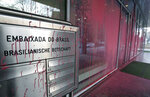 The entrance of the embassy of Brazil is covered with red color after unknown persons threw paint at the building in Germany in Berlin, Germany, Friday, Feb. 1, 2019. (AP Photo/Michael Sohn)
