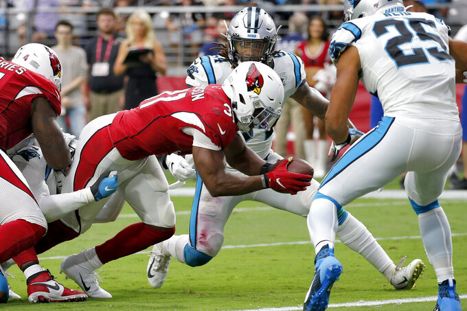 Arizona Cardinals running back David Johnson (31) scores a touchdown as Carolina Panthers strong safety Eric Reid (25) and outside linebacker Shaq Thompson (54) defend during the second half of an NFL football game, Sunday, Sept. 22, 2019, in Glendale, Ariz. (AP Photo/Ross D. Franklin)