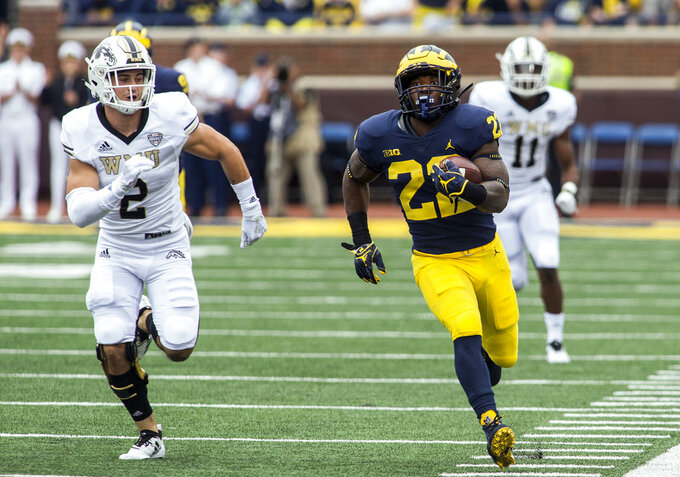 Michigan running back Karan Higdon (22) sprints away from Western Michigan defensive back Justin Tranquill (2) towards the end zone for a 67-yard touchdown run in the first quarter of an NCAA college football game in Ann Arbor, Mich., Saturday, Sept. 8, 2018. (AP Photo/Tony Ding)