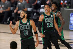 Boston Celtics' Jayson Tatum (0) celebrates after sinking a 3-point basket as Grant Williams (12) and Marcus Smart, rear, cheer him on in the second half of an NBA conference semifinal playoff basketball game against the Toronto Raptors on Tuesday, Sept. 1, 2020, in Lake Buena Vista, Fla. (AP Photo/Mark J. Terrill)