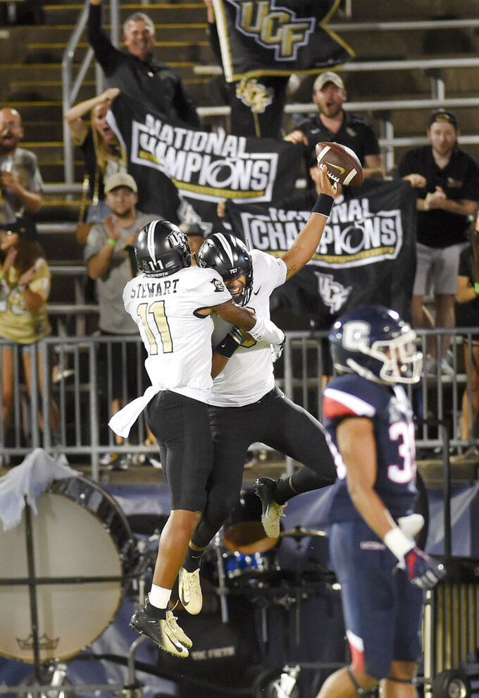 Central Florida quarterback Darriel Mack Jr. (8) is hugged by wide receiver Cam Stewart (11) after Mack scored the team's eighth and final touchdown late in the fourth quarter during an NCAA college football game against Connecticut on Thursday, Aug. 30, 2018, in East Hartford, Conn. UCF won 56-17. (AP Photo/Stephen Dunn)